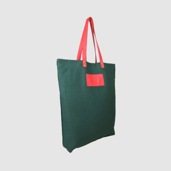 custom premium tote bag in green canvas with pink handles and badge