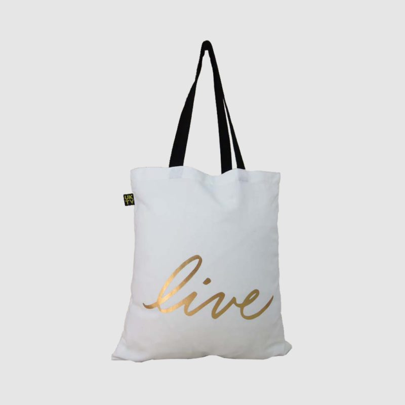 gold print on bag in white canvas with black handles and woven logo label
